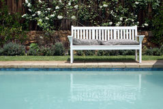 Bench and pool. A bench with cushions beside a cool pool Stock Photos