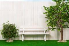 Bench por la cerca con un árbol y los arbustos Fotografía de archivo
