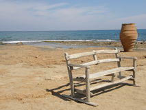 A bench and a pot on the seashore. A wooden bench and a big earthenware pot  on the seashore in Crete island, Greece; sea and sky background Stock Image