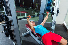 Bench press girl flat multipower Smith machine. Bench press woman on flat multipower Smith machine workout exercise at gym Royalty Free Stock Images