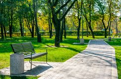 Bench in a quiet city park. Bench near the path of pavers in a quiet city park early autumn on a sunny day Stock Images
