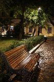 Bench rain night street, light in the foliage stock image