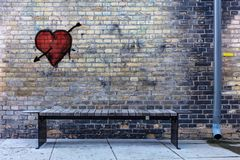 Bench and a rain pipe in a dark corner heart on the wall royalty free stock photography