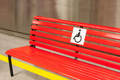 Bench of red color for disabled people in the public building Royalty Free Stock Images