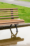 A bench and reflection in the park after the rain Royalty Free Stock Image