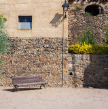 The bench for the rest of the ancient walls. Old street lamp in the village of Pubol. The shadow of the lamp. The medieval wall of the building. Stone wall Royalty Free Stock Images