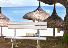 Bench for rest under a straw sunshade on the seashore. Mauritius Stock Images