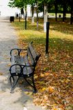 The Bench of the road. Retro black bench on a park with leafs fall down stock image