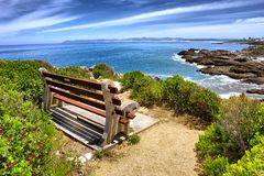 Bench on rocks under dramatic skies Stock Images