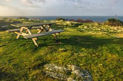 Bench on a rocky shore during a sunset. Bench on a rocky shore of Sweden, during a sunset with a view to the sea Stock Images