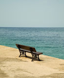 Bench by the sea . Empty wooden bench with a viewpoint looking out to sea Royalty Free Stock Photography