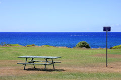 Bench at the sea. Bench and table on gras by the ocean Royalty Free Stock Image