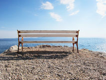 Bench at the sea (6). A white bench at the coast of the blue sea with blue sky and clouds Stock Photos