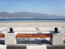 A bench on the sea-front. With a view of mountains royalty free stock photos