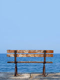 Bench with sea view. Old wooden bench on the seaside overlooking the blue ocean Royalty Free Stock Photo