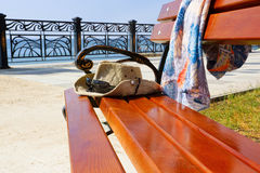 A bench by the sea.Waterfront city of Sudak. Crimea. Hat and shirt to be on a wooden bench.bench on the background of the sea Stock Image