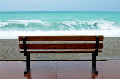Bench and sea waves. Bench and storming sea in the rain Royalty Free Stock Photos