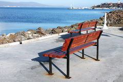 Bench on the seafront. Wooden brown bench standing on the promenade of a sea gulf Royalty Free Stock Photo