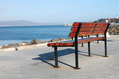 Bench on the seafront. Wooden brown bench standing on the promenade of a sea gulf Royalty Free Stock Photography