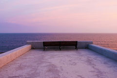 Bench at the seaside. Bench standing alone on a seaside pier at sunset Stock Image