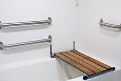 Bench seat on handicap tub. Wooden bench seat on a handicap  bathtub for the disabled Stock Image