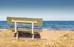 Bench seat overlooking the beach in New Zealand. Royalty Free Stock Photography
