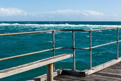 A bench seat on the Port Noarlunga Jetty looking out to the rough seas and reef in South Australia on 6th September 2018 stock photos