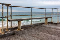 A bench seat on the Port Noarlunga Jetty with no people in South. Australia on 23rd August 2018 stock images