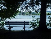 Bench in the Shade. Park bench and trees as silhouette with a view of the Weissensee in Bavaria Stock Photos