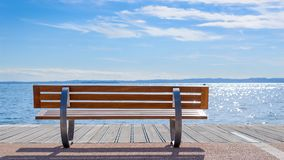Bench on shore of Garda lake Royalty Free Stock Image