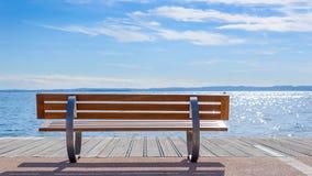Bench on shore of Garda lake Royalty Free Stock Image