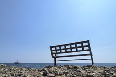 A bench on the shore and a ship in the sea. The coast of the ancient city of Lycia. Stock Image