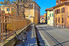 Bench on sidewalk and road through town in Italy. Royalty Free Stock Image