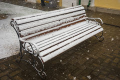 A bench smoothly covered with fresh snow after weather phenomena. Closeup view of a bench smoothly covered with fresh snow after weather phenomena - snowfall in Stock Photo