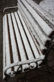 A bench smoothly covered with fresh snow after weather phenomena. Closeup view of a bench smoothly covered with fresh snow after weather phenomena - snowfall in Royalty Free Stock Photography