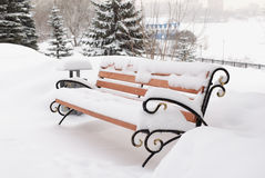 Bench in snow-covered winter park Stock Photos
