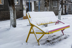 Bench in snow covered winter town yard Royalty Free Stock Image