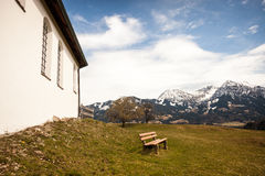 Bench with snowcapped mountain range in spring Royalty Free Stock Photo