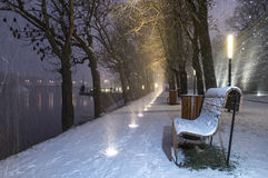 Bench. Snowfall at nights wiht lights Stock Photos