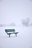 Bench in snowy park Stock Photos