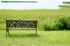 Bench sobre a grama verde no lago Imagens de Stock Royalty Free