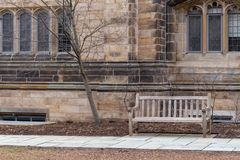 Bench on stone walkway against old decorative building stock photo