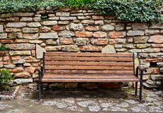Bench and stone wall Stock Photo