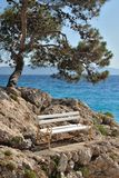 Bench on stones over the sea. Podgora, Croatia Royalty Free Stock Images