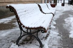 The bench on the street covered by snow. Winter time Royalty Free Stock Photography
