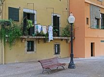 A bench and street lantern on the background of colorful facade of the building and a balcony with plants in Girona. Girona, Spain - 12 September, 2014: A bench royalty free stock photo