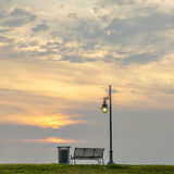 Bench beside a street light at sunset Stock Photography