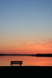 Bench at Sunset. An empty bench silhouetted on the beach at sunset Royalty Free Stock Image