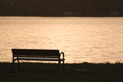 Bench Sunset. A park bench and sunset reflected in the waters Royalty Free Stock Images