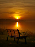 Bench and sunset. Wooden bench and sunset over lake Stock Image